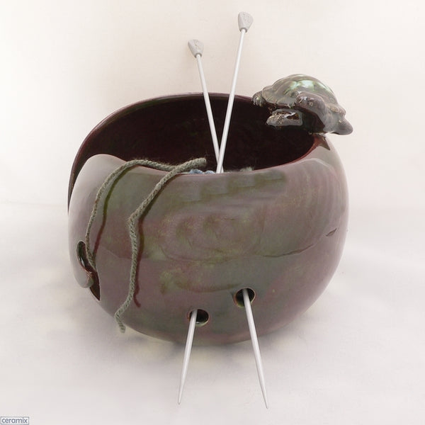 Tortoise Destiny Large Round Yarn Bowl shown with wool and knitting needles. Handmade by Margaret Melville Hugo from African clay and speciality glazes at Ceramix