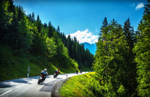 Bikers in mountainous tour, traveling across Europe, curve highw