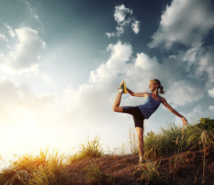 Young slim lady doing stretching exercises on a rural path with