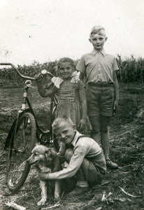 Vintage photo of three children with a dog and a bike - thirties