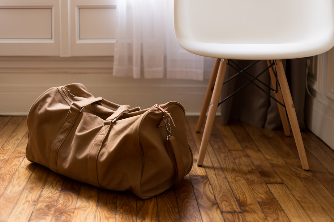 Brown canvas duffle bag sitting on floor