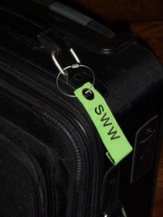 Personalized Neon Green Luggage Tag on Black Suitcase