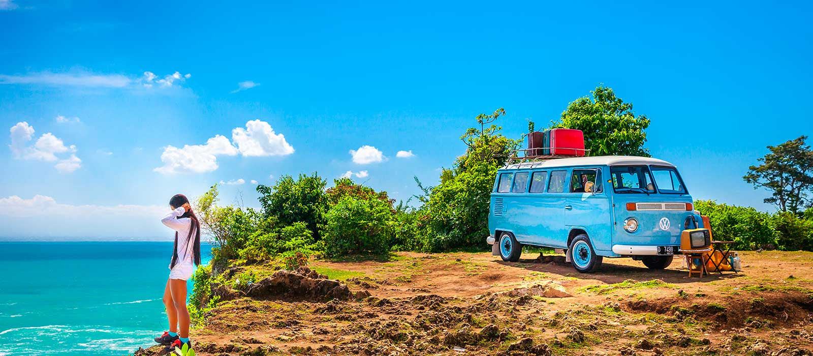 Girl on sea cliff edge next to bright blue VW camper