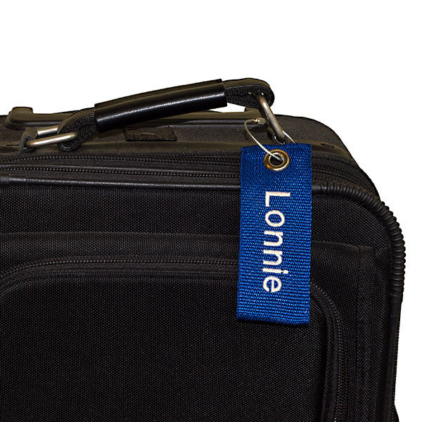blue extreme bag tag with white text shown on suitcase
