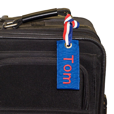 Custom blue luggage tag on suitcase from YourBagTag