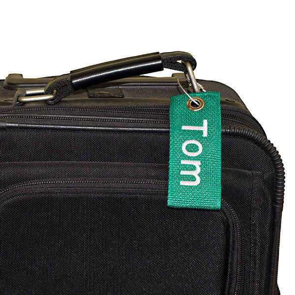 green extreme bag tag with white text shown on suitcase