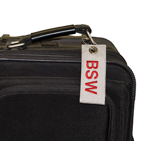 gray extreme bag tag with red text shown on luggage