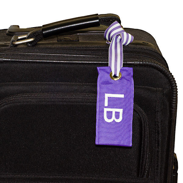 Personalized light purple luggage tag shown on suitcase