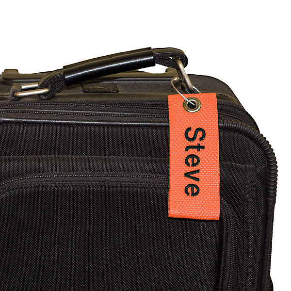 orange extreme bag tag with black text shown on bag