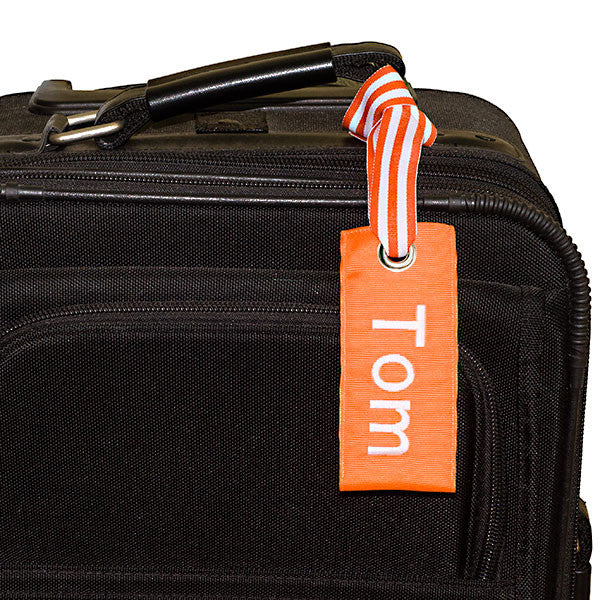 orange custom luggage tag shown on black suitcase