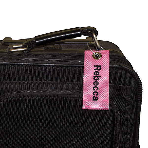 pink extreme bag tag with black text shown on luggage