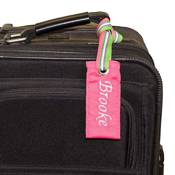 Personalized pink luggage tag shown on black suitcase