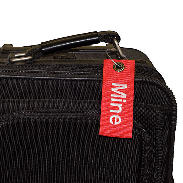 red extreme bag tag with white text shown on bag
