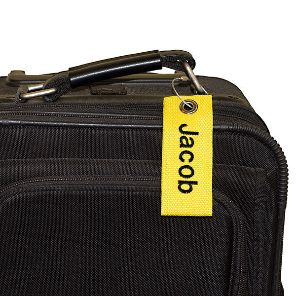 yellow extreme bag tag with black text shown on luggage