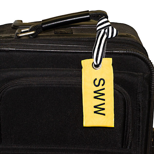 Sunny yellow custom luggage tag shown on suitcase