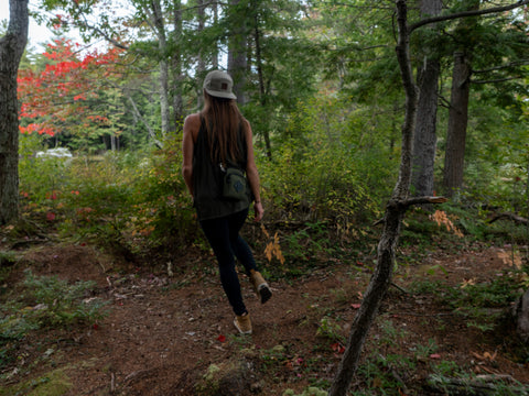 An active girl walking through the trails during foliage with a green treefort lifestyles forager bag and tan canvas canopy cap