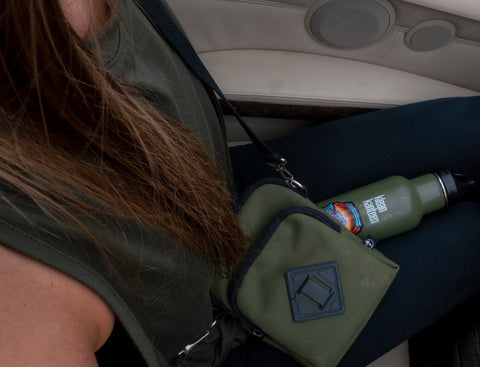 cute girl sitting in car with water bottle and treefort lifestyles forager bag on lap
