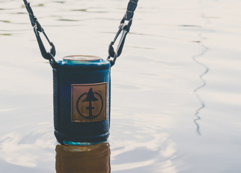 a close up of the deluxe crows nest coozie keeping a canned beverage cool by hanging it in the water.