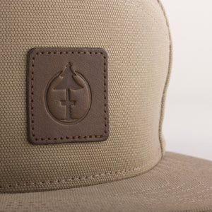 Leather de-bossed detail of the Treefort Lifestyles Canopy Cap in tan canvas, made in the USA.