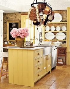 Yellow farmhouse kitchen with stainless steel farmhouse sink