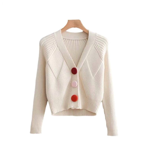 Cropped ivory cardigan sweater with oversized, colorful fabric buttons.