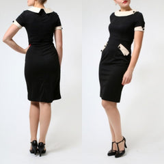 This black and cream hourglass dress features a lovely portrait collar, front pockets and decorative buttons.