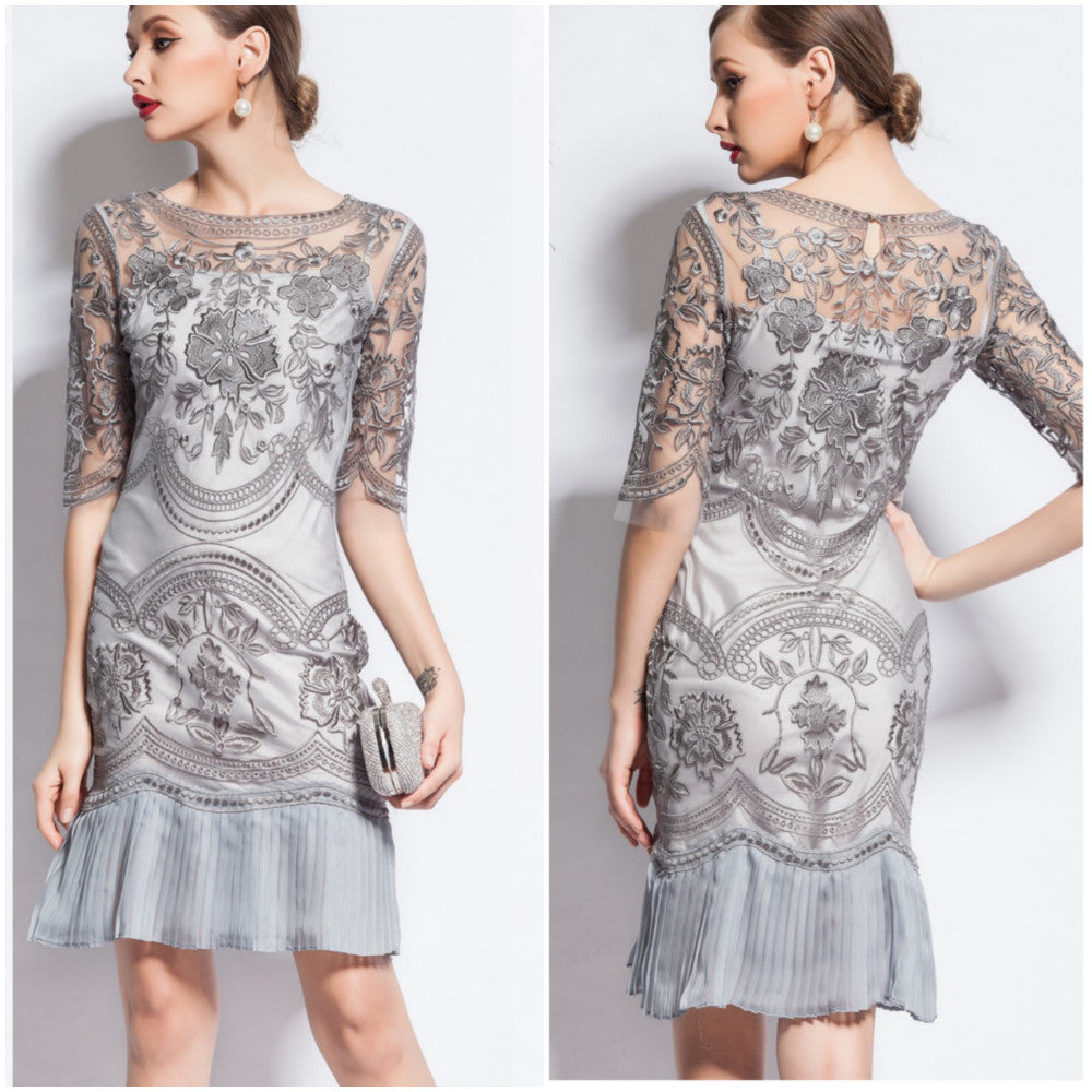 "An exquisite rendering of the 1920's ""flapper"" sheath dress, this dove gray stunner features a meticulously hand-embroidered tulle and floral overlay."
