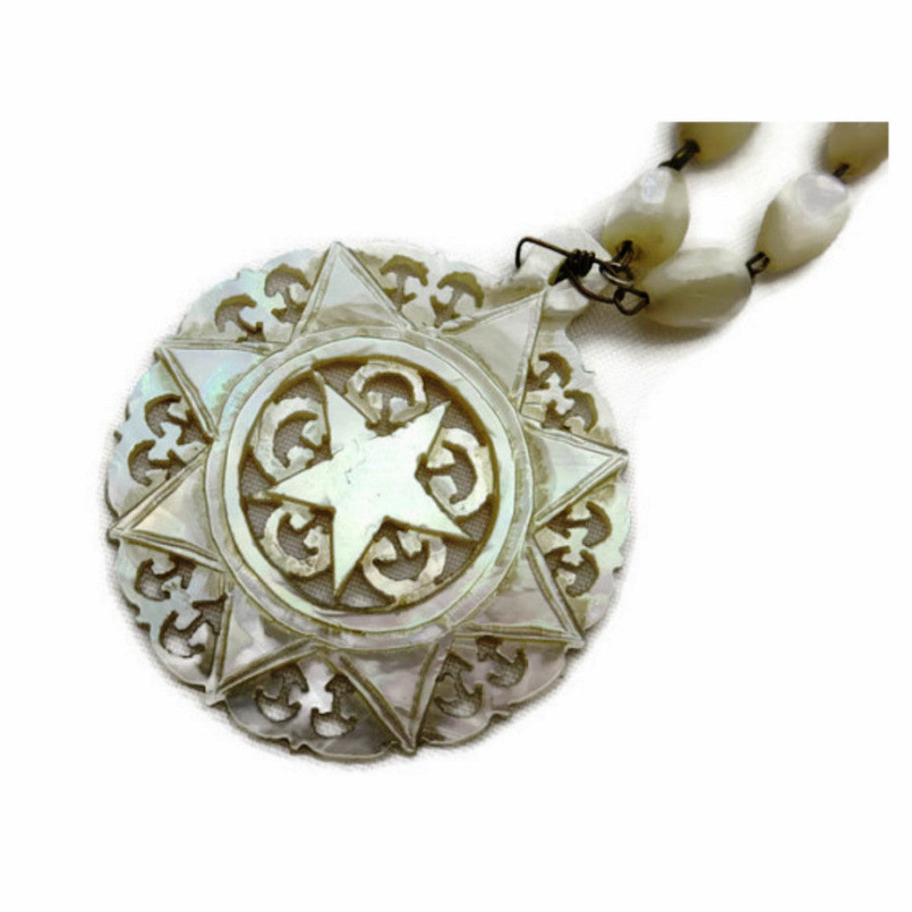 Antique mother of pearl necklace with carved star pendant.