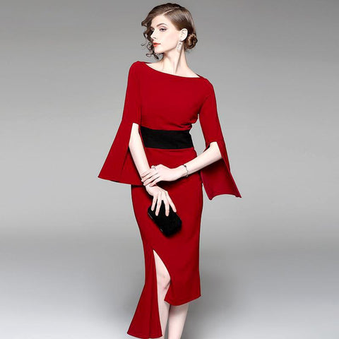 Deep red asymmetric sheath dress with split bell sleeves.