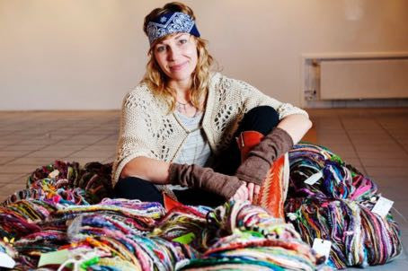 True Fiber Addict: Woman surrounded by colored yarn and wool