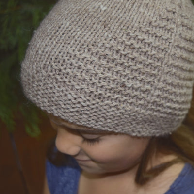 Child wearing Aviary Hat Pattern knit in rose gray