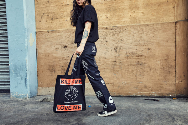 Image of model wearing black tshirt and black custom Coloured pants, holding tote bag.