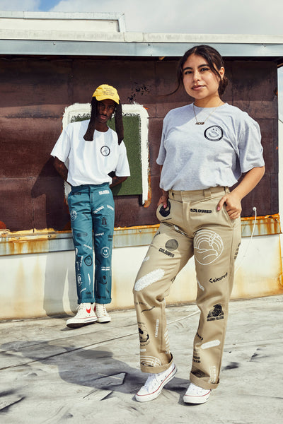 Image of two models wearing yellow Coloured hat, white Coloured tee, light green custom Coloured pants, and gray Coloured tee and khaki custom Coloured pants.