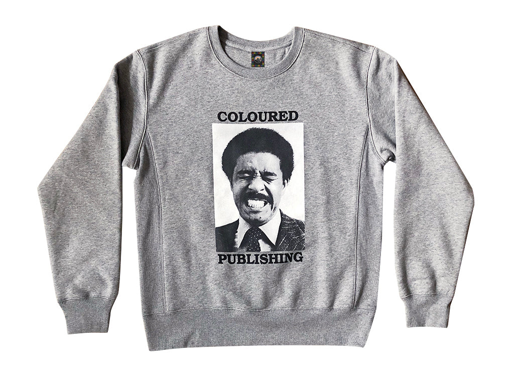 "Image of a gray crewneck sweater with ""Coloured"" printed above a black and white image of a grimacing man, above the word ""Publishing"""