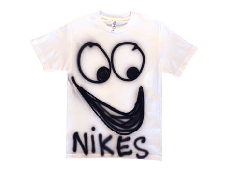 "Photo of an airbrushed t-shirt with a smiley face and ""Nikes"" by artist Devin Troy Strother."