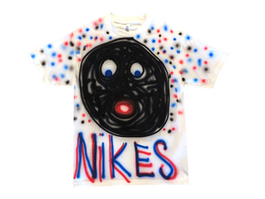 "Photo of an airbrushed t-shirt with a smiley face and the word ""Nikes"" by artist Devin Troy Strother."