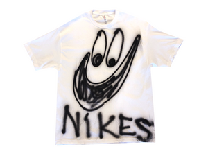 "Photo of an airbrushed t-shirt with a smiley face with the word ""Nikes"" by artist Devin Troy Strother."