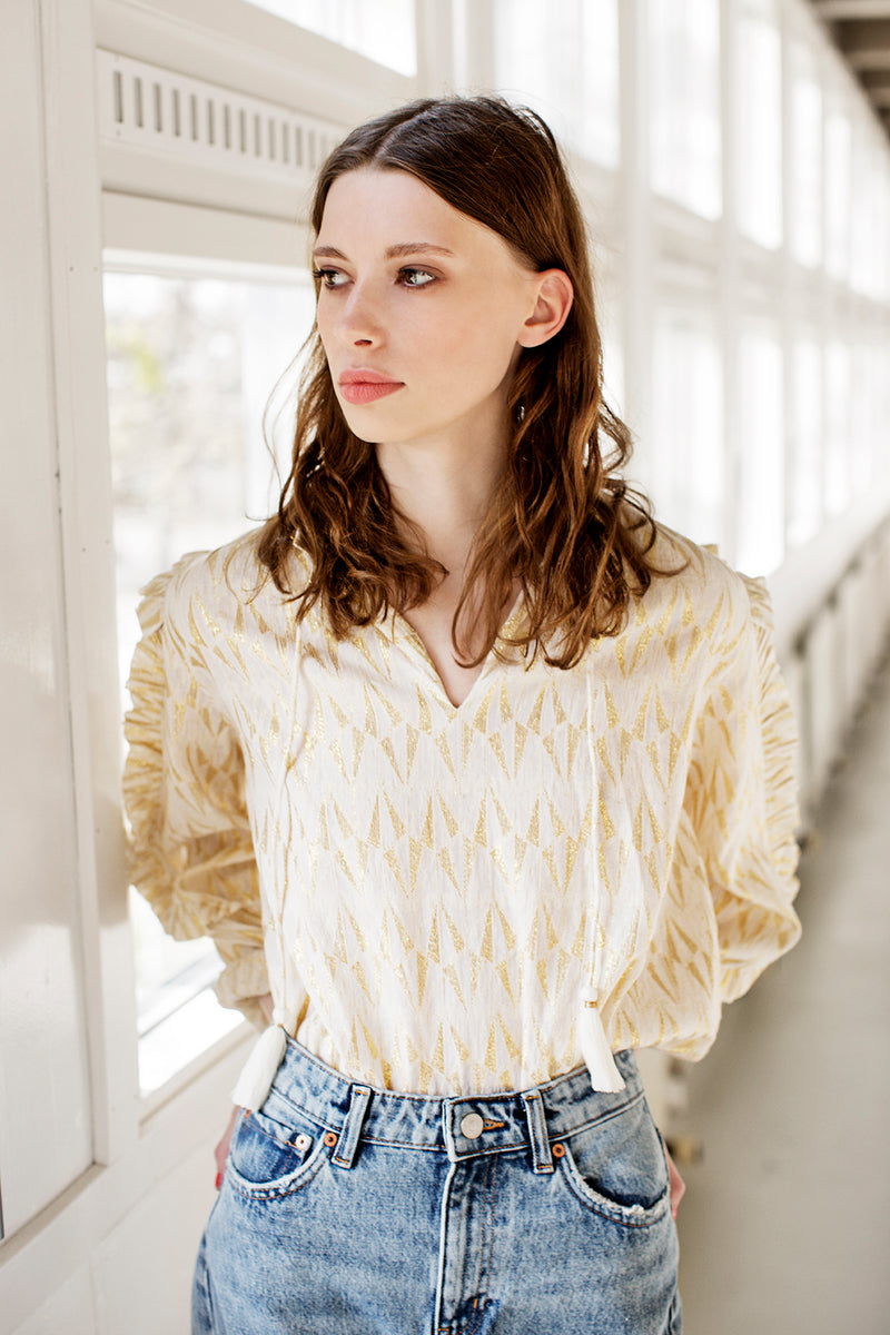 Linea shirt with gold details, drawstring and ruffled sleeves styles with jeans