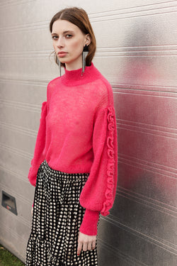 Lone hand knit blouse in pink with ruffles on sleeves and styled with Lucy black white skirt
