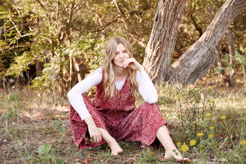 Model wearing the Estella Corduroy Jumpsuit, sitting down in a park with a white long sleeve underneath