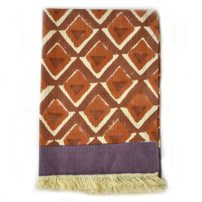 Block print geometric diamond waffle weave cotton hand towel with a fringe end.