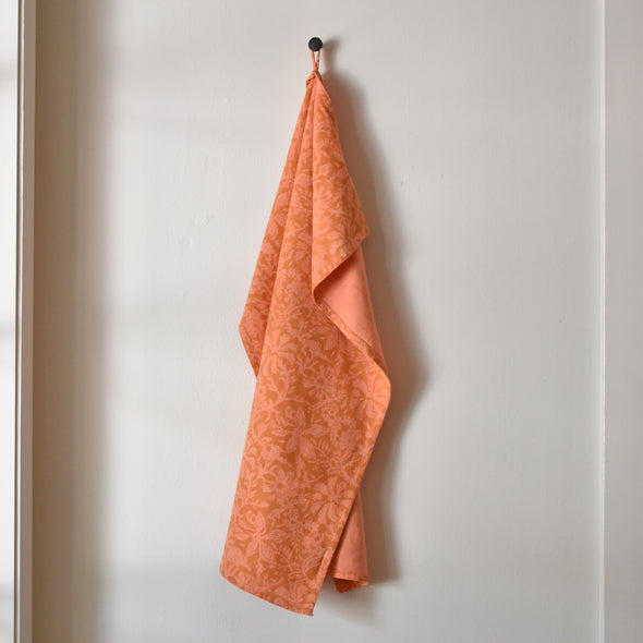 Block print orange floral cotton kitchen towel with two loops.