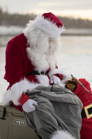Santa putting on his Orvis Ultralight Waders with Calgary's Fly Shop