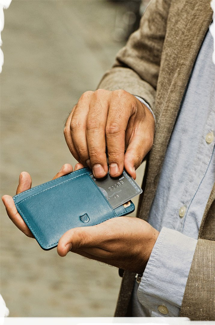 Man sliding credit card into leather front pocket wallet.