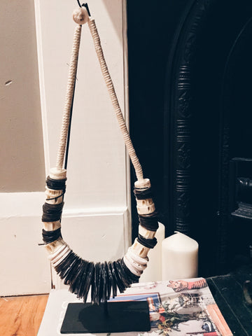 BLACK AND WHITE TRIBAL PEACE NECKLACE ON STAND