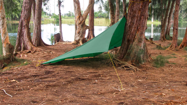 To set up this mode, tie one end of the tarp ridgeline as high as you can reach on a tree. Next, stake out two corners on the tree end of the tarp and then the corners and center on the other end