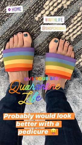 Close up shot of feet wearing rainbow Pride Slides