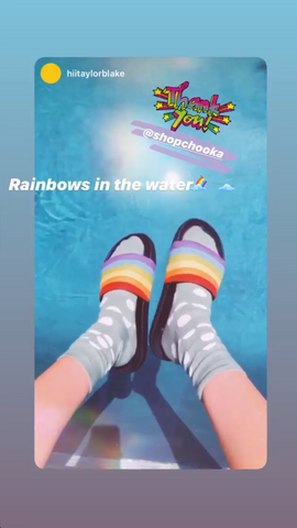 Feet with socks and rainbow Pride Slides hanging over an outdoor pool