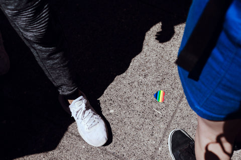 Looking down at shoe next to a rainbow heart sticker on the ground