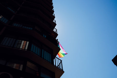 Looking up at a rainbow pride flag coming out a building